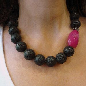 This is a stunning statement necklace. Black lava stones create a very unique piece and a chunky pink jade stone gives an asymmetrical and modern look