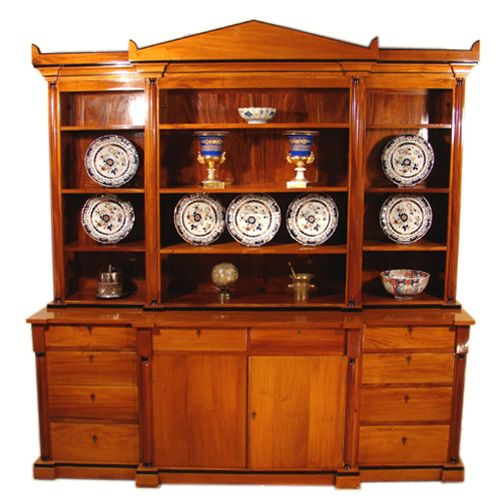 """An attractive Continental Biedermeier stye birch and ebonized breakfront bookcase, the architectural pediment above open shelves with cupboards and drawers below flanked by half columns, raised on a plinth base. Circa 1880.  H: 86""""  W: 83 1/2""""  D: 22""""  $9,500"""