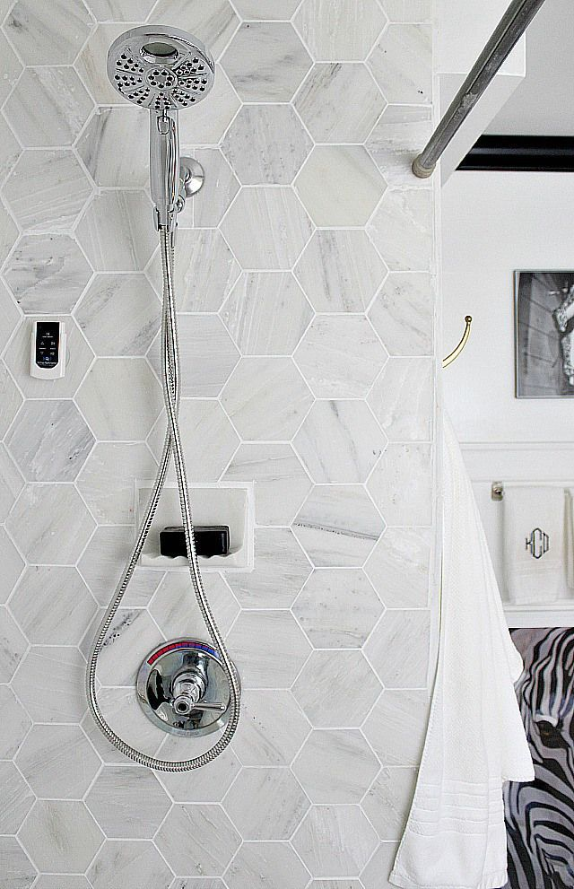 Bathroom makeover via Bliss at Home:  Black and white bathroom remodel with Carrara marble hexagon tile, white vintage tub, Delta faucet chrome shower head,  and Homewerks Bluetooth bath fan with speakers.