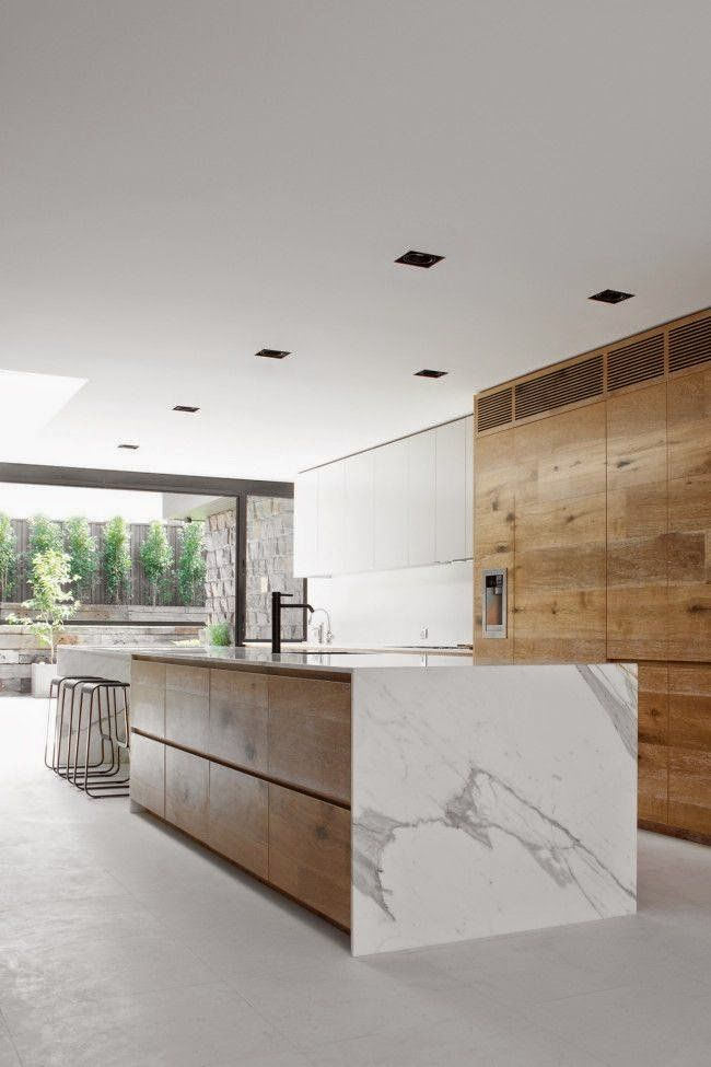Cucina minimal moderna con armadi in legno non rifiniti e isola in marmo di Carrara