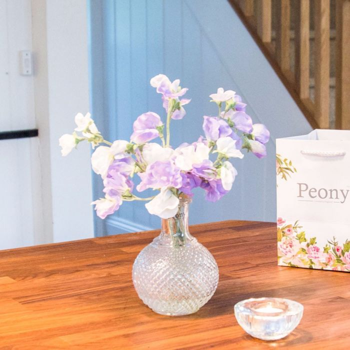 Isn't this just the sweetest little piece? The cream and purple petals of these delicate faux Sweet Peas are a truly gorgeous combination, complemented so wonderfully by our beautifully-crafted Vintage Bottle Vase. Presented in a limited edition '30 Years of Peony' gift bag, this pretty display will make a perfect gift or a delightful feature to your home.