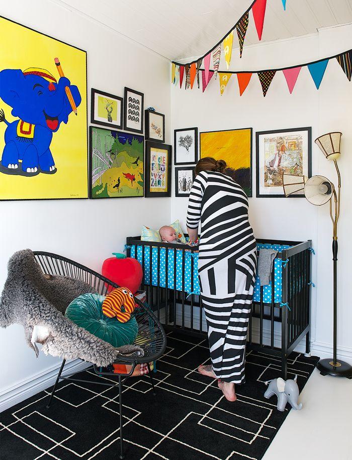 Även i Franks rum är väggarna täcka med tavlor. Vimplarna har Eva sytt. Fåtölj från Åhléns, sittpuff, Rice.