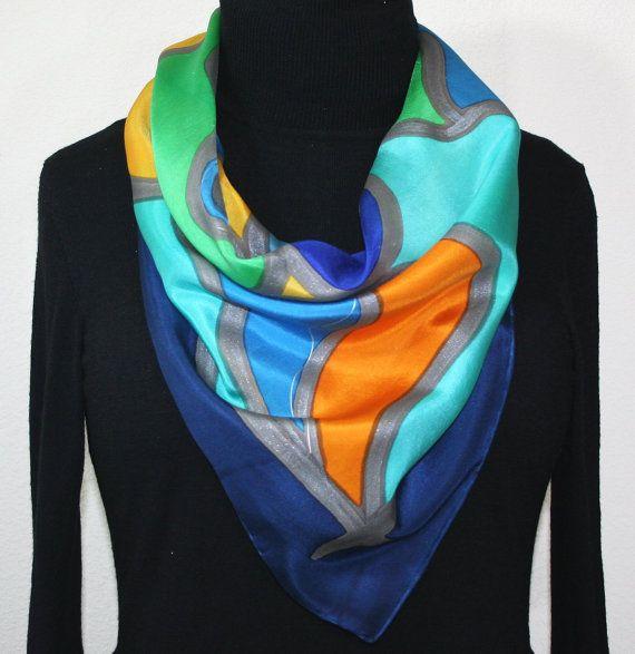 Zijden sjaal Hand geschilderd. Blauw, groen, oranje zijden sjaal. Handgemaakte sjaal. Gelukkige herinneringen sjaal. Formaat 30 x 30 vierkant. Zijden sjaals Colorado. Hand geverfd sjaal 100% zijde. Made in USA.  MADE TO ORDER sjaal. Aangeboden in twee maten  Dit is een 100% Habotai zijden sjaal, met abstracte vormen in tinten van staal blauw, royal blauw, turquoise, groen, oranje en donker geel. Contouren zijn in tin, met dunne spiraal accenten in zilver. De grens van de sjaal is…