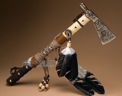 This is a rustic metal Native American style tomahawk made by the Tarahumara Indians.This decorative tomahawk has a fully wrapped handle with fur and feathers. The head of the tomahawk is crafted from