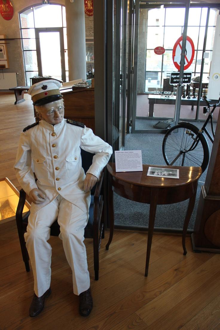 Figur af Vilhelm Bay, den sidste tolder på de Dansk-Vestindiske øer, iført sin tropeuniform. Et brud på det dengang gældende uniformsreglement for Det danske Toldvæsen, der dikterede mørkegrøn, ulden uniform.