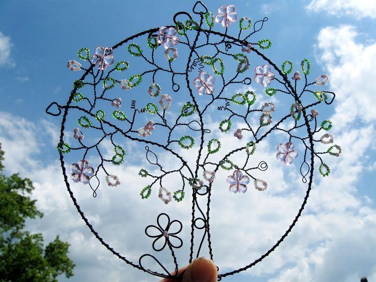 Jarní nálada Stromek udrátovaný z černého žíhaného drátu září zelenými,růžovými a bílými skleněnými korálky v několika odstínech a růžovými akrylovými květy. Vyjímá se hezky zavěšený na zdi, v prostoru i na okně, kde sluníčko krásně rozehraje barevnou hru skleněných korálků. Velikost dekorace je cca 18 cm.