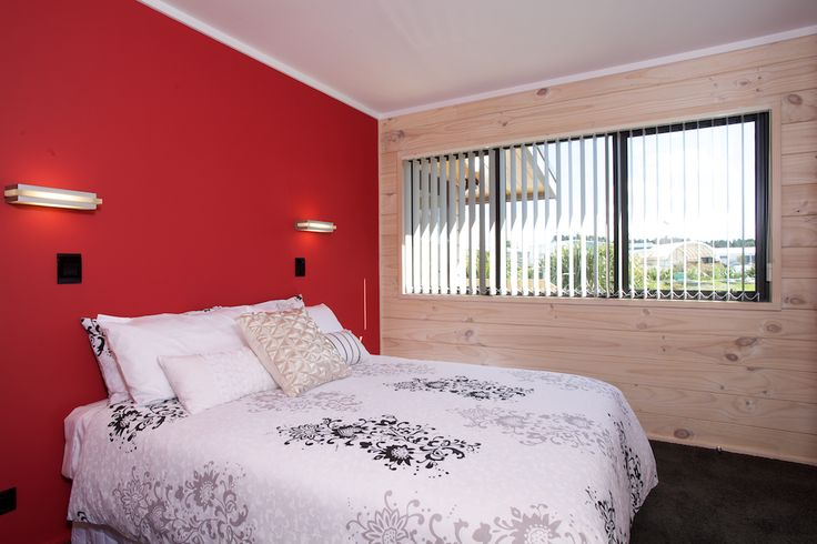 Second bedroom stunning red feature wall in Lockwood Kaipara show home in West Auckland