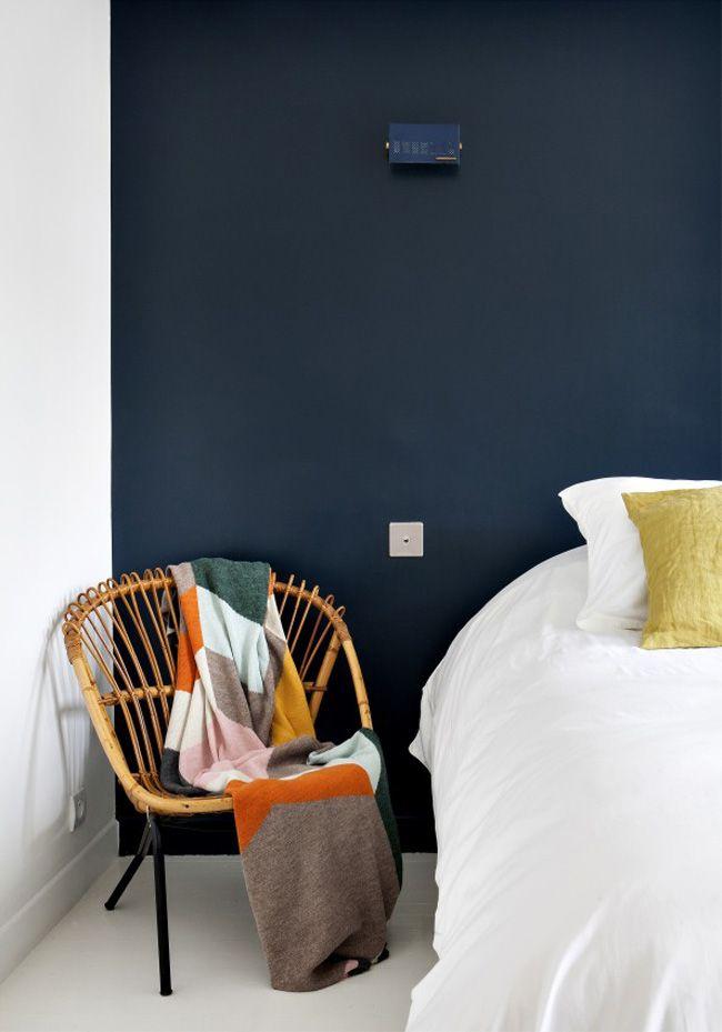 la décoration d'une chambre de l'hôtel Henriette situé à Paris : un mur peint dans un bleu marine plein de nuances, une chaise en osier et métal et un grand lit blanc                                                                                                                                                     Plus