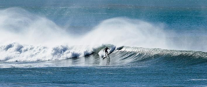 Surfer at Wainui Beach, north of Gisborne, on the East Coast of New Zealand.