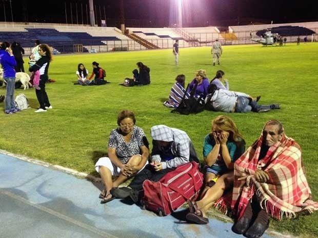 Apesar do frio, moradoresde Iquique  passam noite em gramado de estádio. (Foto: Aldo Solimano / AFP Photo)