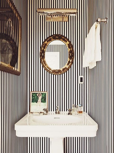 Striped wallpaper, oval mirror, sink vanity, decorative objects...in hte bathroom barefootstyling.com