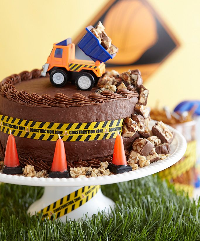 A store-bought chocolate cake gets  the construction zone treatment with a dump truck unloading Snickers pieces and cone-shaped candles.