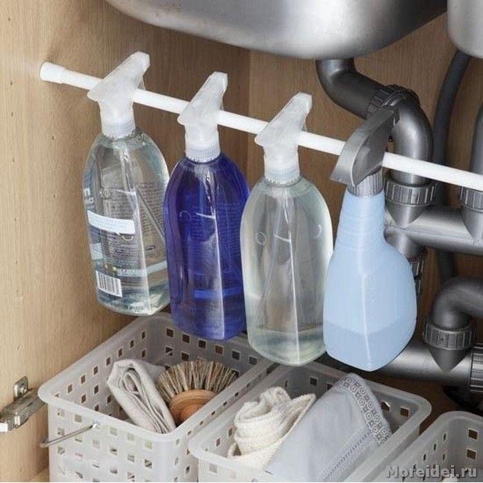 Установите стержень под раковиной и храните на нем бутылки с чистящими средствами.