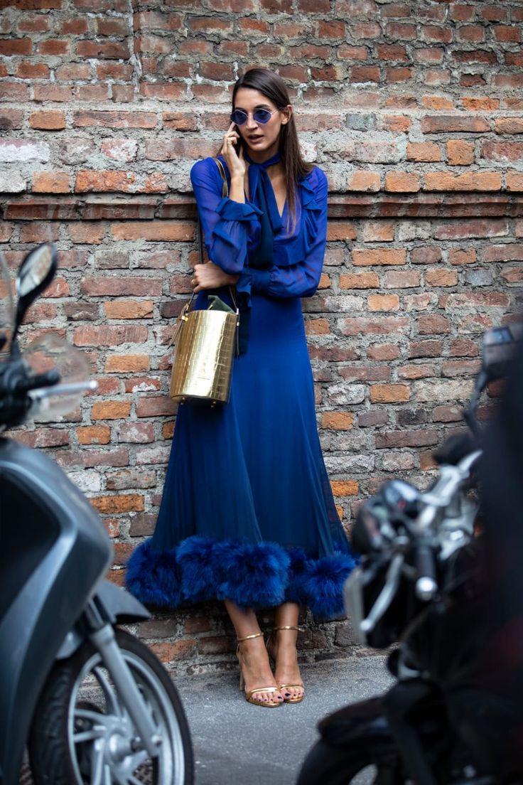 Langärmliges blaues Midikleid mit blauem Fellbesatz. Goldene Riemchensandalen und