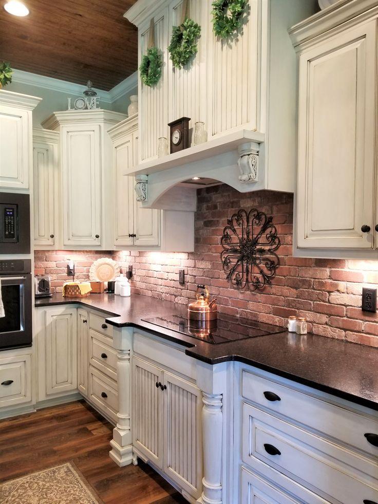 Farmhouse kitchen with brick backsplash and white cabinets ...