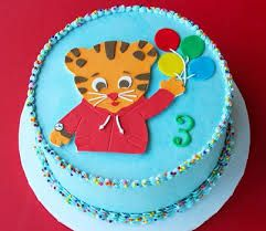 I like the Daniel Tiger image with face and sweater on this cake. I also like the sprinkles.