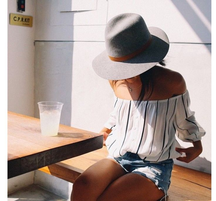 white and black striped off the shoulder top with cut off jean shorts and grey hat. casual summer style.