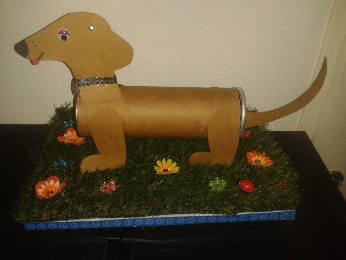 Een lief hondje op een grasveldje vol bloemen. Kadootjes zitten in de hond ( staart kan eraf) en onder het gras.