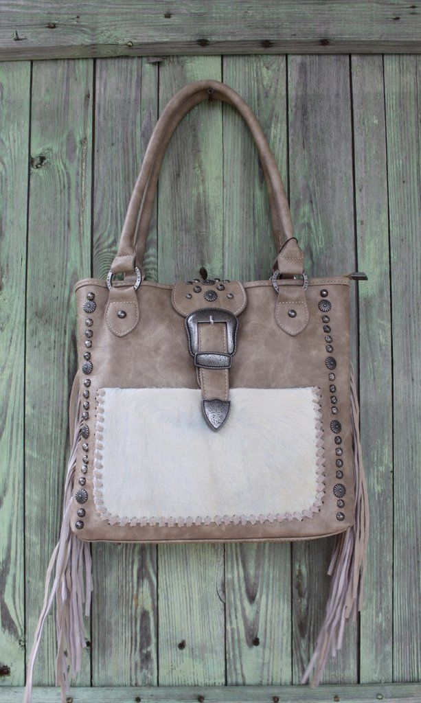 Concealed carry handbag in beige. Fur pocket stitched across the front. Dual carrying handles. Genuine leather mixed with man-made leather. Interior is fabric lined with multiple pockets. Top zip clos