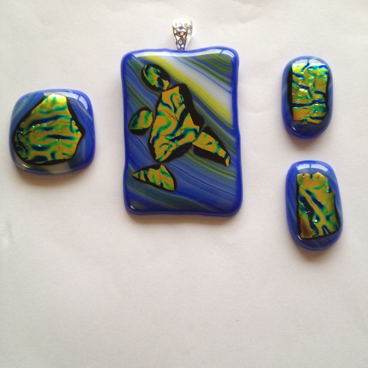 New.. Three Part sets: Matching pendant, broach and earrings. Dichroic orange, gold and green, in a blue wavy glass base. $100.00AUD the set.