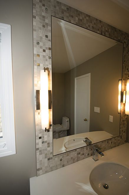 mosaic tile mirror frame with modern light fixtures on either side