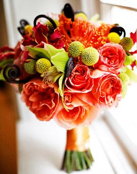 For the fall bride who isn't afraid to use color, a vibrant trio of garden roses, cymbidium orchids and gloriosa lilies is combined with orange pin cushions, fern curls and billy balls