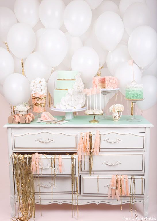 This charming table included three cakes in shades of mint and peach by Jenna Rae Cakes on a pretty white chest of drawers. Gold glittering streamers and stark white balloons completes this lovely display. www.onefabday.com