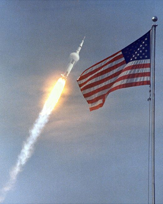 Apollo 11 Liftoff and Flag - A Saturn V rocket launches the Apollo 11 crew on the first moon landing mission on July 16, 1969 in this image framed by an American flag.  Four days later, Apollo 11 astronauts Neil Armstrong and Buzz Aldrin landed on the moon while crewmate Michael Collins orbited above.