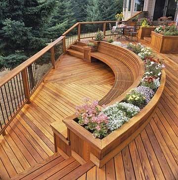 je ziet hier een terras, van hout. met bloemen bakken