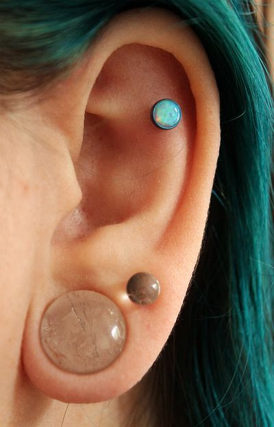 Outer conch piercing. Anatometal 5mm light blue opal cab set in teal titanium.  Double lobe piercing. Stretched lobe.