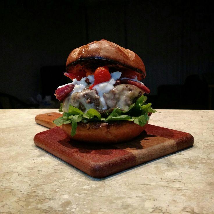 Burger bovino de 180g, queijo gruyere e mozzarella, aioli de iogurte e mel, tiras de bacon, rúcula, pimenta biquinho e pão de batata.