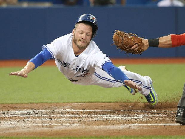 Josh Donaldson slides safely across home plate to score on a sacrifice fly in the second inning.