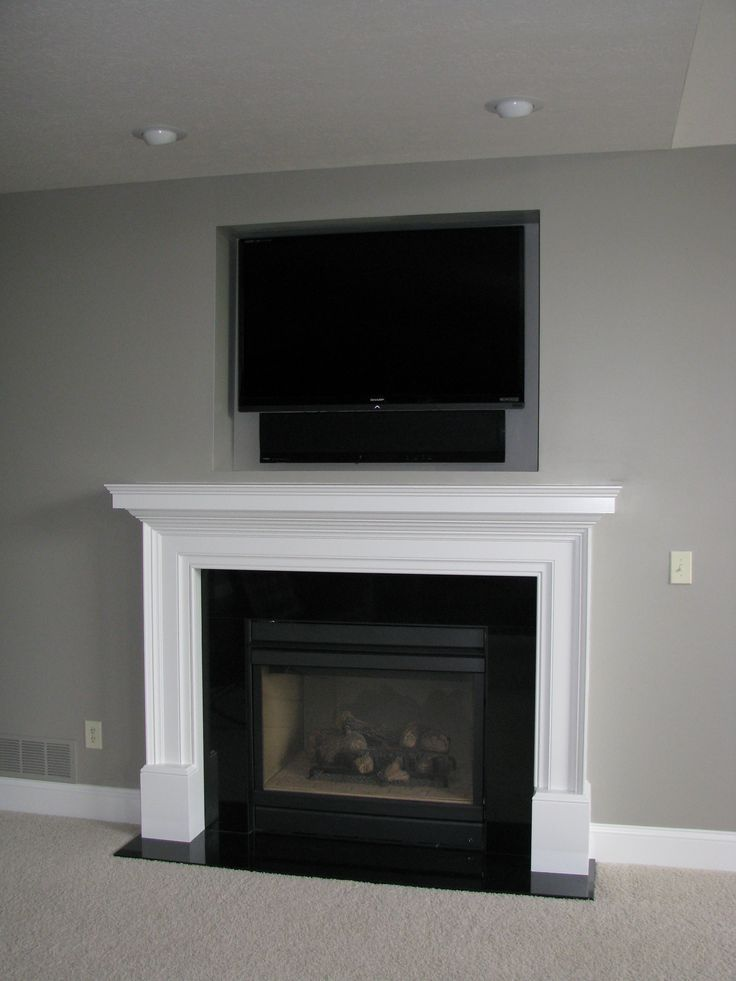 Recessed above a fireplace, a Sharp HDTV and Yamaha Surround Sound Projector.