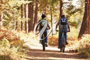 Couple mountain biking through forest, back view full length