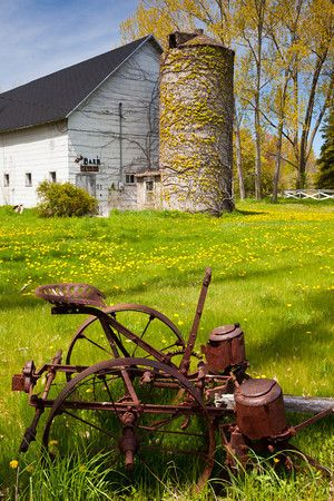 Old farming equipment lays in a field near a Door County barn. Northport, WI