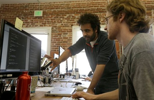 Shereef Bishay, co-founder of Dev Bootcamp, center, talks with student Ryan Guerrettaz during a class at Dev Bootcamp in San Francisco. Image: AP Photo, Jeff Chiu