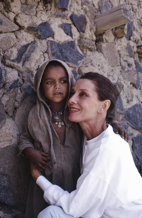 Audrey Hepburn...    UNICEF Goodwill Ambassador Audrey Hepburn hugs a small girl who is standing in the shade of a large stone wall in the town of Mehal Meda in the northern part of the province of Shoa, Ethiopia. © UNICEF/NYHQ1988-0194/John Isaac  http://www.unicef.org