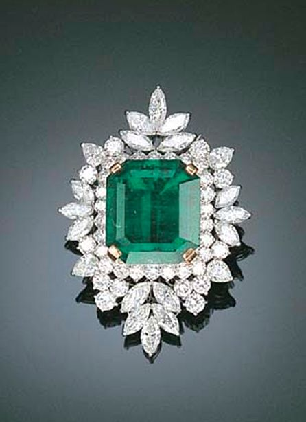AN IMPORTANT EMERALD AND DIAMOND PENDANT/BROOCH Set with a cut-cornered rectangular-cut emerald in the pear-shaped, marquise and circular-cut diamond cluster surround, mounted in white gold, 5.0 cm high