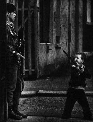 A child points a stick gun at a British soldier in Belfast, Northern Ireland. Photo by Stan Grossfeld.