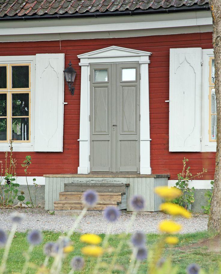 Mot faluröda hus är det väldigt vackert att måla entrédörren i en varmgrå nyans som ovan.