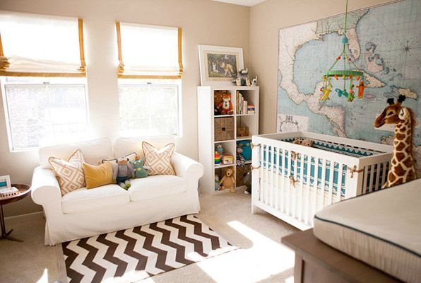 Beautiful nursery design with tan walls, white rolled-arm slip-cover convertible sofa, West Elm Zig Zag Rug, David Hicks La Fiorentina Pillow in Tan, FAO Schwarz Gentle Giant Giraffe, white roman shades with yellow ribbon trim, West Elm Jacks Table in Sheesham, Serena & Lily Rye Crib Set, Pottery Barn Map Wall Decal and Blabla Jungle Mobile.   For the adventurer!