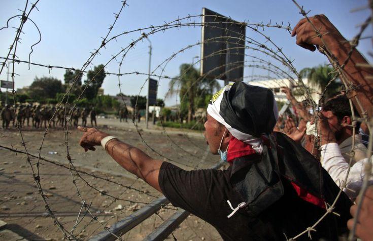 Partidarios del expresidente egipcio Mohamed Morsi increpan a miembros del ejército egipcio en el exterior de la sede de la Guardia Republicana, en El Cairo, 8 de julio de 2013. KHALIL HAMRA (AP)