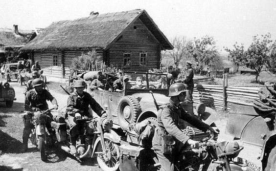 """A convoy of motorcyclists """"Totenkopf"""" in Russian village. The eastern front."""