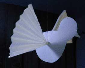 Rita upp en duva på vitt kraftigt papper. Skär en skåra för vingarna enligt bilden. Vik ett tunnare papper som ett dragspel. Trä in p...