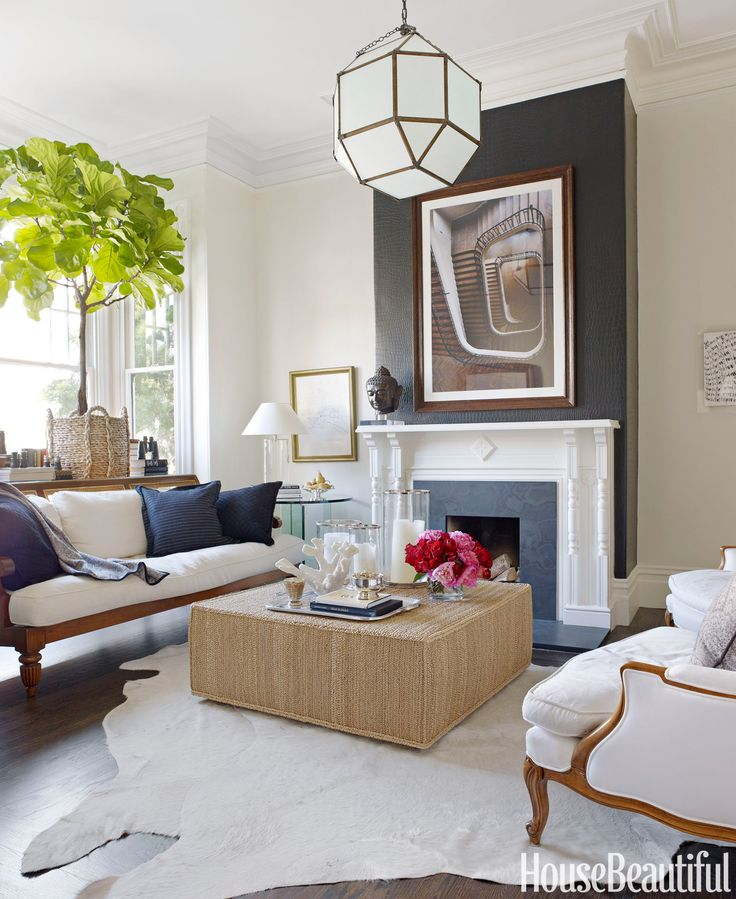 Antique meets modern in the living room of a San Francisco Victorian. Designer Ken Fulk chose a black and white palette, softened with neutrals and natural textures. The chimney breast is papered with Ralph Lauren's black Yacare Crocodile, and a Ralph Lauren Peyton ottoman sits on a cowhide rug from Frank's Leather & Hides.   - HouseBeautiful.com