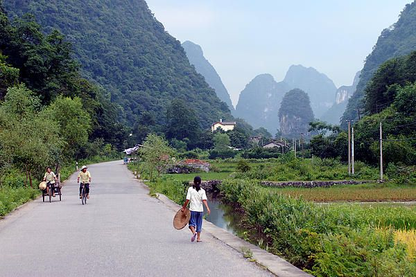 Yangshuo is situated in south central China, in Guangxi, bordering on Vietnam. The northern border of Yangshuo is formed by the Li River. I hired a bicycle and set out for a spin on the surrounding back roads on a humid 36 degree Celsius afternoon. Dripping with sweat as I moved in the opposite direction, it occurred to me that the woman with the hat that walked past me would be a nice focal point set against the backdrop of the karst peaks that dominate this area. #Guilin, #karst…