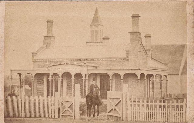 Ballarat Lutheran Manse CDV by G. Willetts of Sturt Street, Ballarat, Victoria. Sign reads 'Deutsch Lutheranisches Pfarrhaus'. From Heritage Victoria: Architect, Frederick Poeppel, designed this characteristically Tudor styled manse in 1868 for the Ballarat Lutheran church. Executed in face brickwork (painted) it has similarity with Poeppel's Anglican parsonage in Castlemaine(1864) with its capped gable ends, drip moulds and stuccoed chimney shafts set on the diagonal.