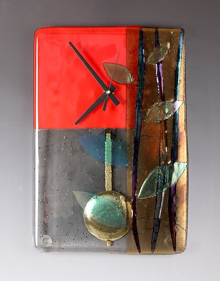 Fused glass clock boldly colored in red with bronze & black iridescent colors, set off with graceful leaf motifs. Pendulum adds a subtle movement to this Asian inspired piece.