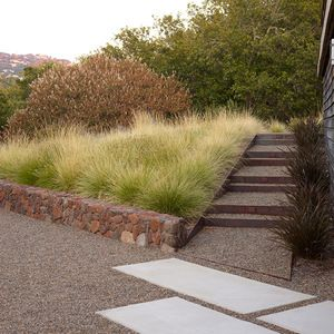 Low stone wall/slight slope w. grasses, Corten & pebble stair/path lined with dark Phormium on the right.