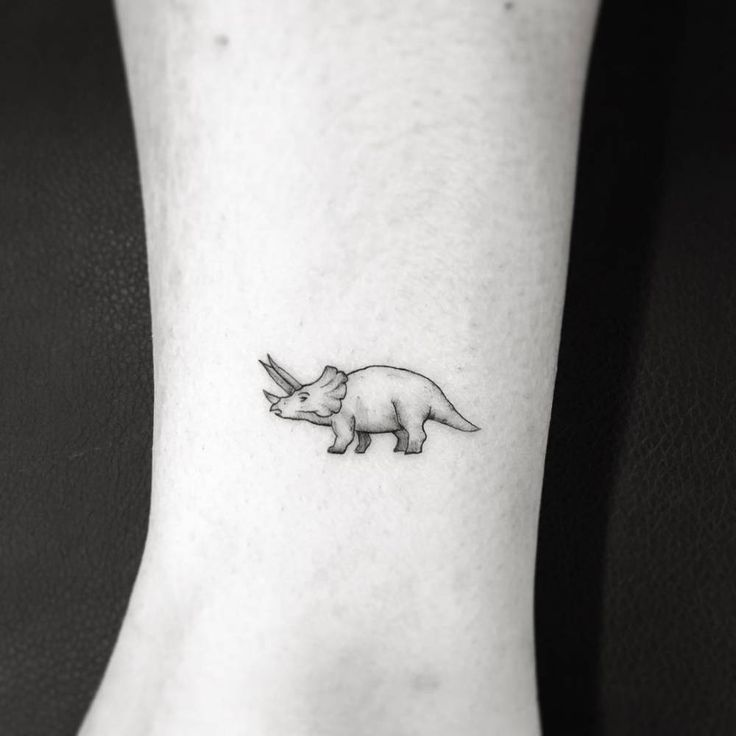 """1,5"""" triceratops dinosaur tattoo on the ankle."""